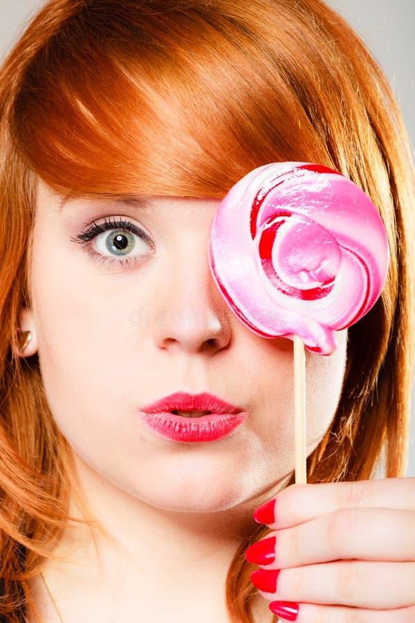 Redhair-Mädchen mit rosa Lutscher stockfoto
