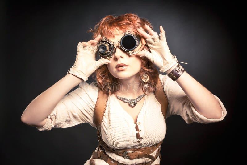 Redhair steampunk vrouw met beschermende brillen stock afbeelding