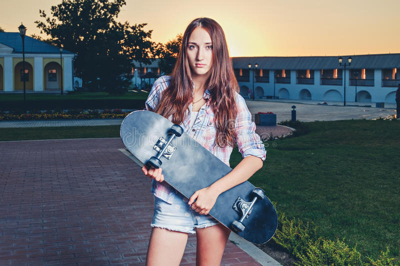 Redhair teen girl holding skate board before her stock images