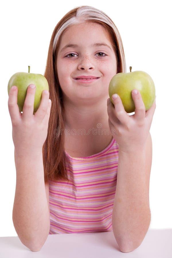 Redhaired dziewczyna z zielonym jabłkiem fotografia royalty free
