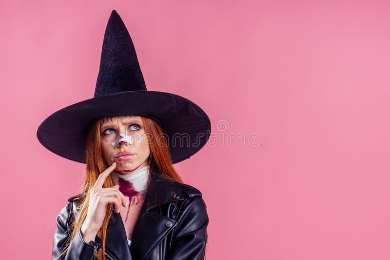 Redhaired ginger woman witch black hat and in leather jacket take thought and scaring with crazy make up on her pretty royalty free stock photography