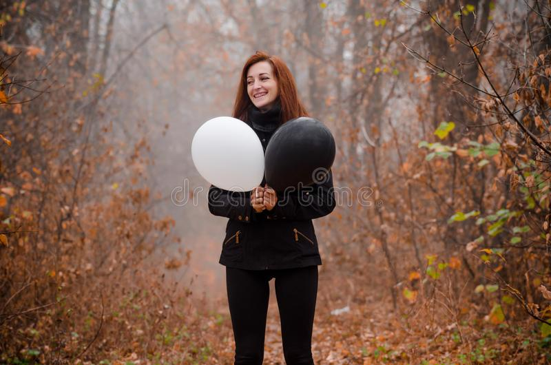 Redhaired girl in the autumn forest loughing and holding black and white balloon. The concept of choice, good and evil stock photo