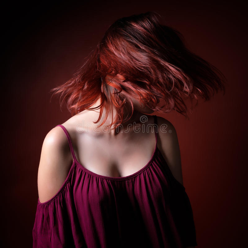 Redhaired girl with her hair floating on the air. Photographed on a red background royalty free stock photography