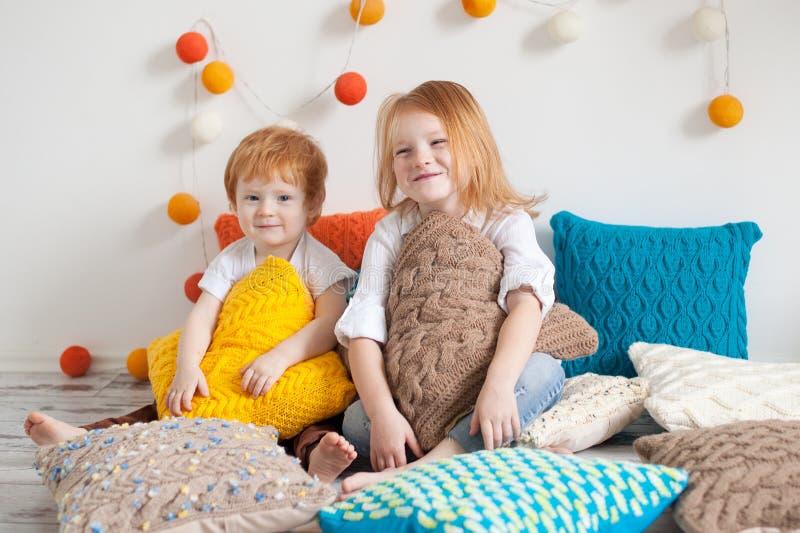 Redhaired Kinder unter Kissen lizenzfreies stockbild