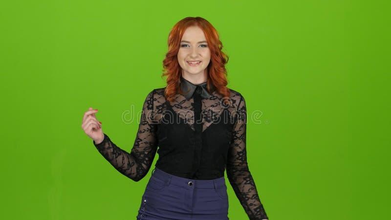 Redhaired meisje begint te dansen, is zij in een goede stemming Het groene scherm stock footage