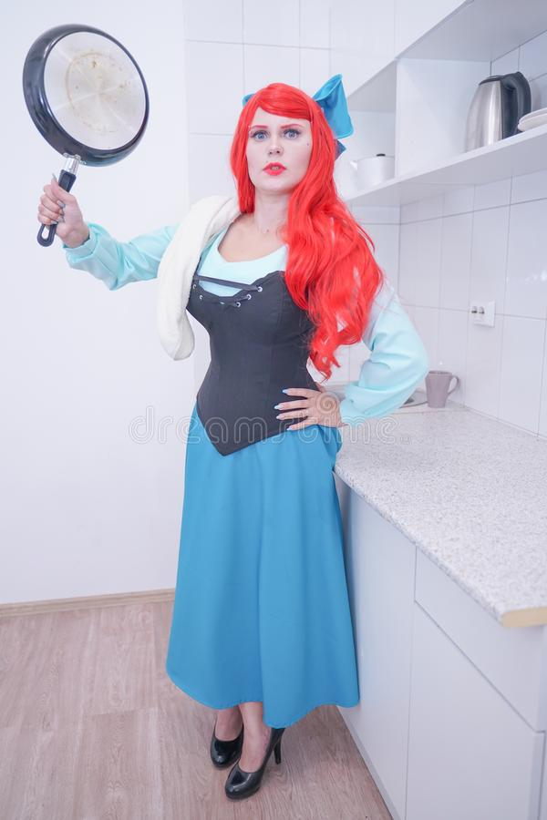 Redhaired plus size angry sad woman holding frying pan. Plump curvy chubby female with red hair in princess mermaid costume with black skillet royalty free stock photo