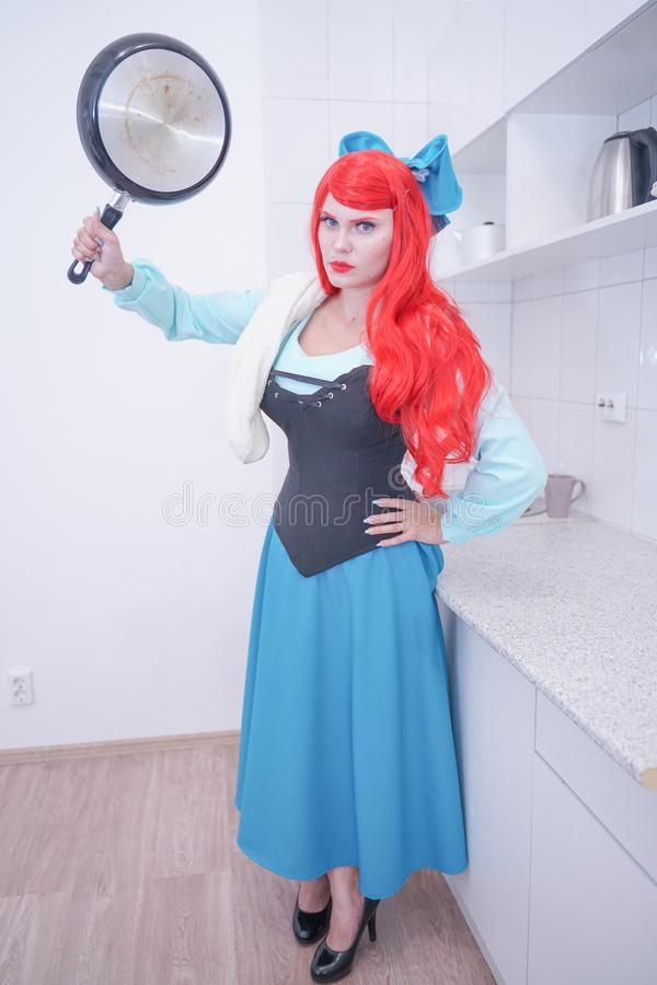 Redhaired plus size angry sad woman holding frying pan. Plump curvy chubby female with red hair in princess mermaid costume with black skillet stock images