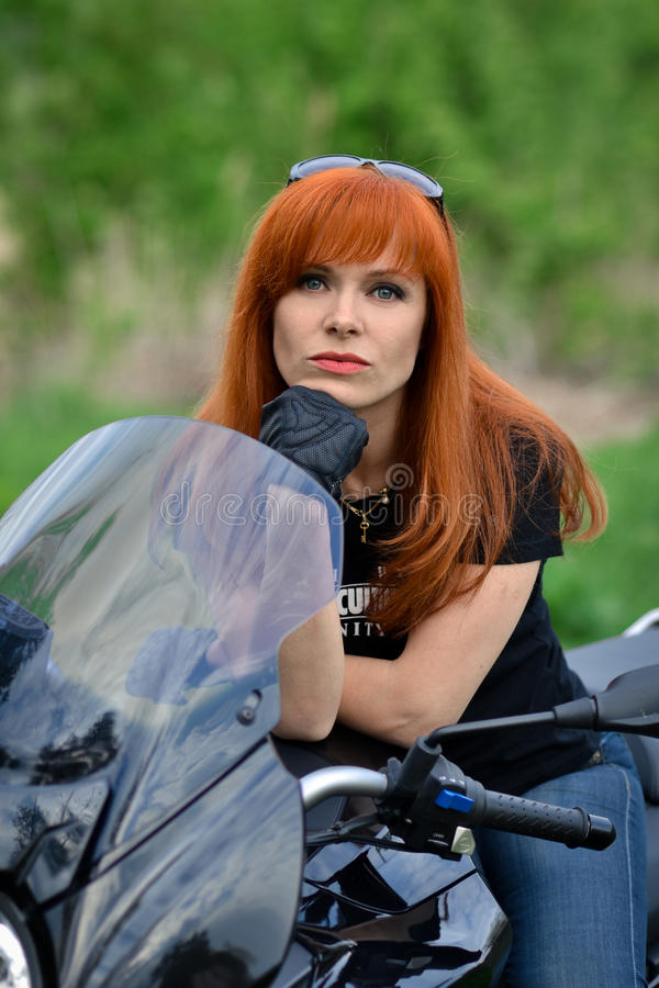 Red-haired,serious,angry,calm,powerful woman in black royalty free stock image