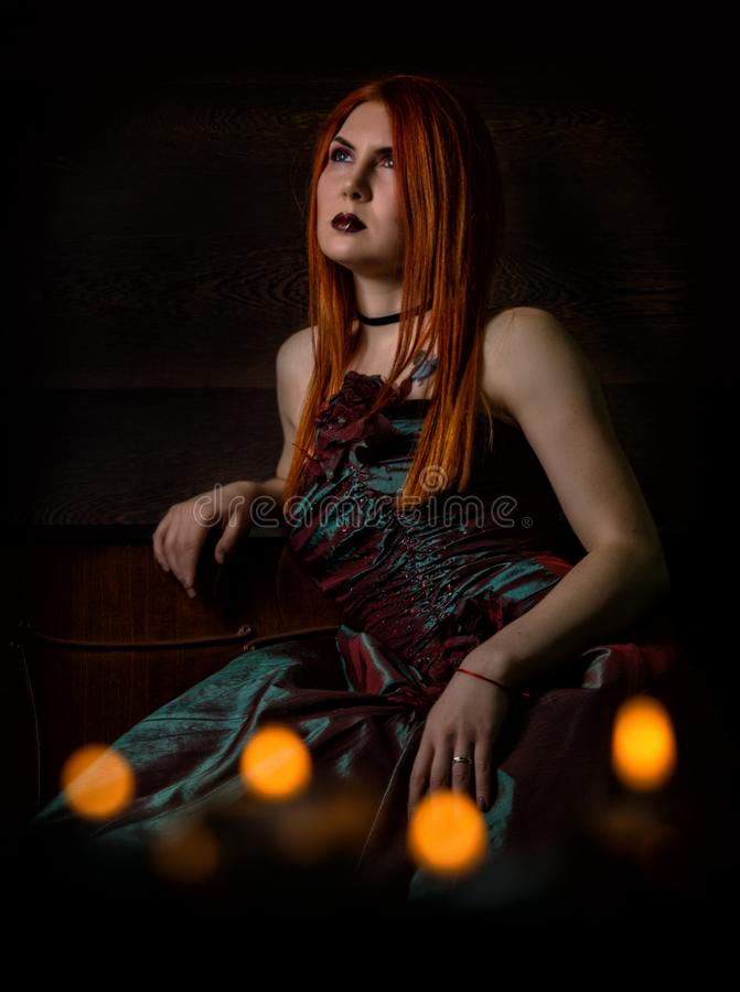 Redhaired woman in a retro dress with candles on black background stock photography
