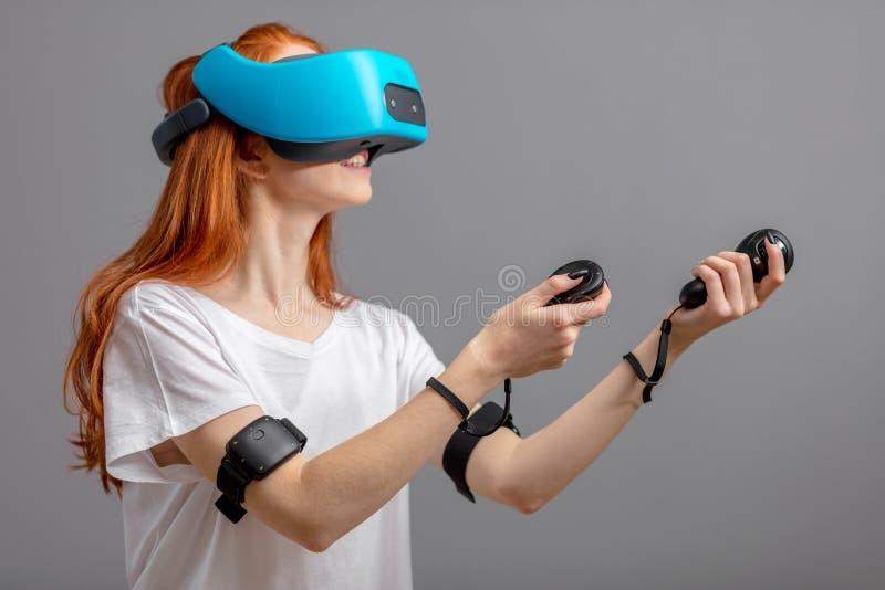 Redhead κορίτσι που χρησιμοποιεί τα γυαλιά VR που απομονώνονται πέρα από το λευκό Εμπειρία εικονικής πραγματικότητας στοκ εικόνα με δικαίωμα ελεύθερης χρήσης
