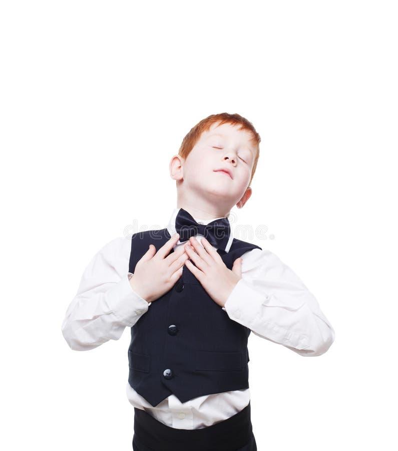 Redhead αγόρι στη φανέλλα με το δεσμό τόξων, ευτυχής και ευχαριστημένος στοκ εικόνες