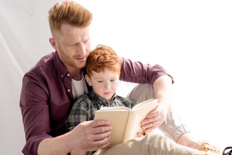 redhead βιβλίο ανάγνωσης πατέρων και γιων από κοινού στοκ εικόνες