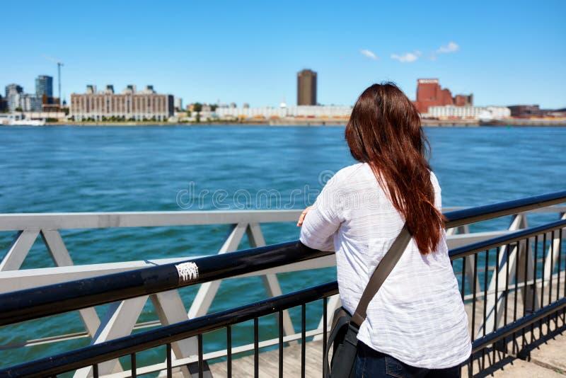 Redhead γυναίκα που προσέχει το τοπίο της πόλης του Μόντρεαλ και του ποταμού Αγίου Lawrence μια ηλιόλουστη θερινή ημέρα στο Κεμπέ στοκ εικόνα