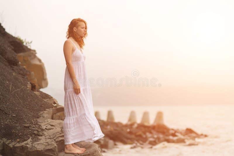 Redhead γυναίκα που στέκεται στην ακτή στην παραλία στοκ φωτογραφία με δικαίωμα ελεύθερης χρήσης