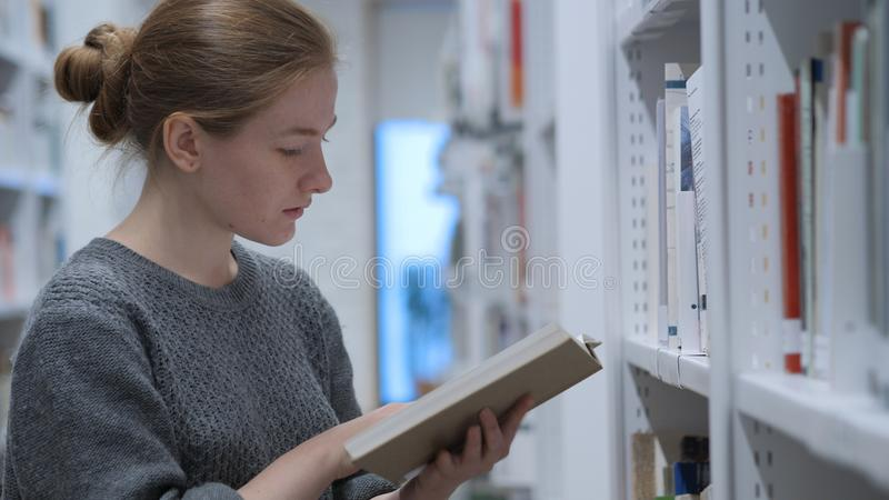 Redhead γυναίκα που ψάχνει και που διαβάζει το βιβλίο στη βιβλιοθήκη στοκ εικόνα με δικαίωμα ελεύθερης χρήσης