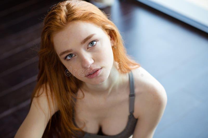 redhead γυναίκα συνεδρίασης πατωμάτων στοκ εικόνα