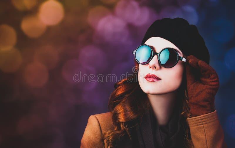 Redhead γυναίκα ύφους στα γυαλιά ηλίου και το παλτό στοκ εικόνες