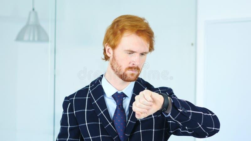 Redhead επιχειρηματίας που περιμένει στην εργασία, χρόνος προσοχής για το ρολόι στοκ εικόνες με δικαίωμα ελεύθερης χρήσης