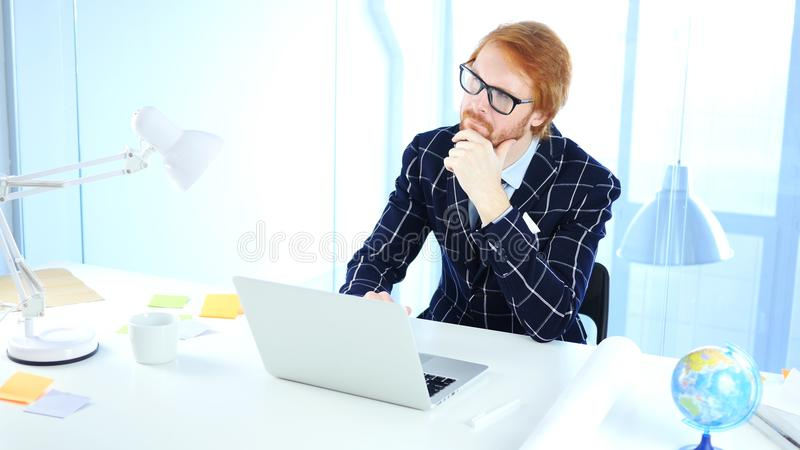 Redhead επιχειρηματίας που σκέφτεται τη νέα ιδέα στην εργασία, δημιουργικός σχεδιαστής 'brainstorming' στοκ φωτογραφία