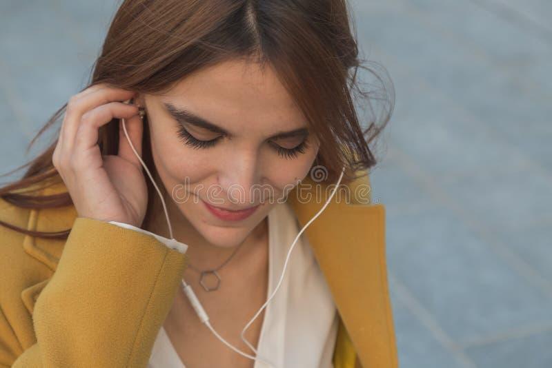 Redhead κορίτσι που ακούει τη μουσική στις οδούς πόλεων στοκ εικόνες με δικαίωμα ελεύθερης χρήσης