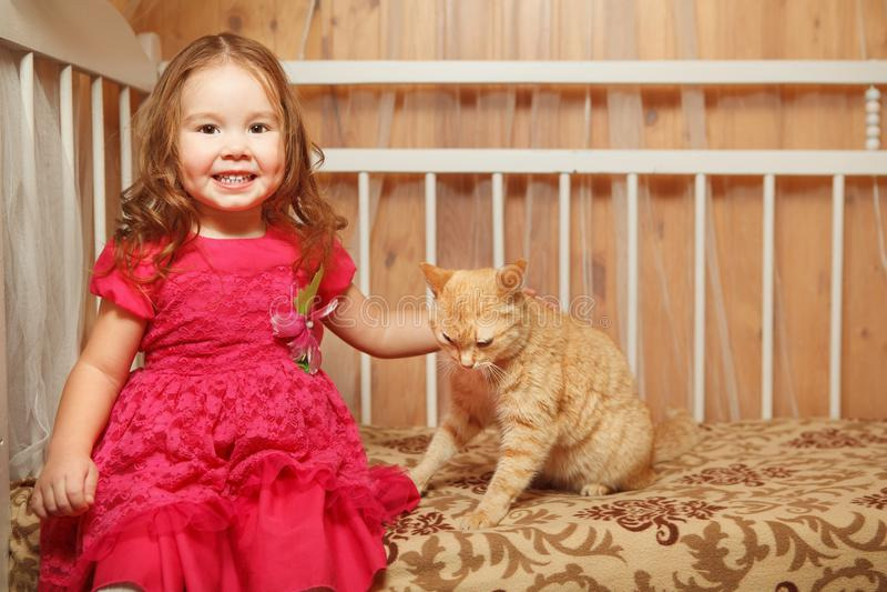 Redhead κορίτσι που κτυπά μια κόκκινη γάτα στοκ φωτογραφία