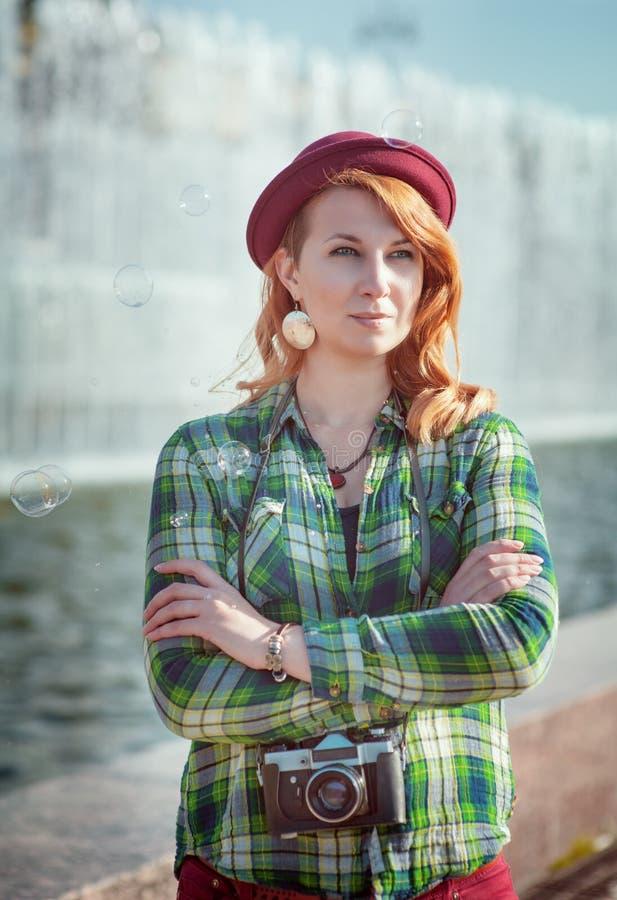 Redhead κορίτσι Hipster στο καπέλο με την αναδρομική κάμερα στοκ εικόνες