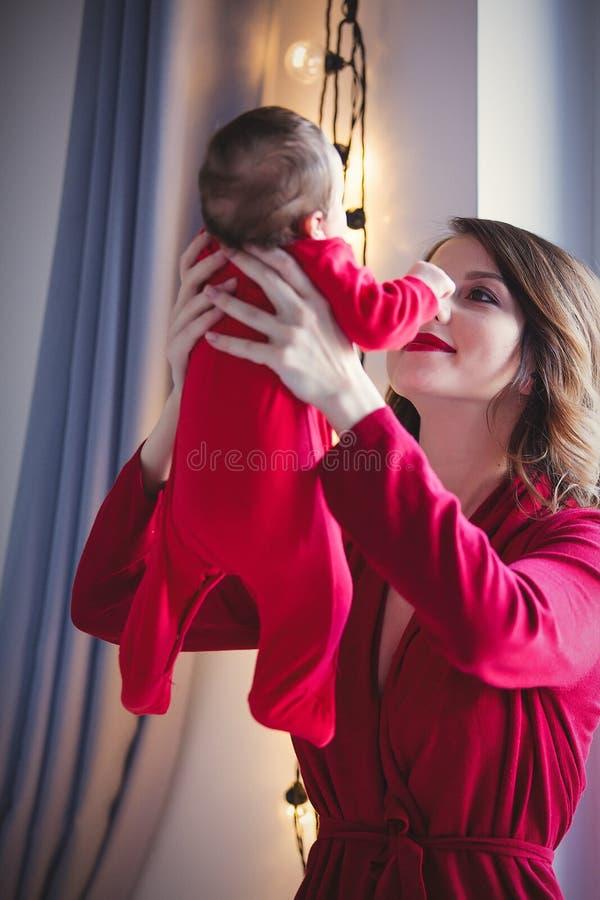 Redhead μητέρα με νέο - γεννημένο παιδί στο κόκκινο στοκ φωτογραφία με δικαίωμα ελεύθερης χρήσης
