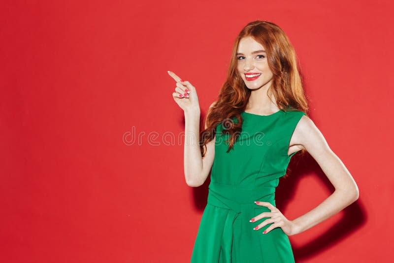 Redhead νέα ευτυχής κυρία στην πράσινη υπόδειξη φορεμάτων στοκ φωτογραφία με δικαίωμα ελεύθερης χρήσης