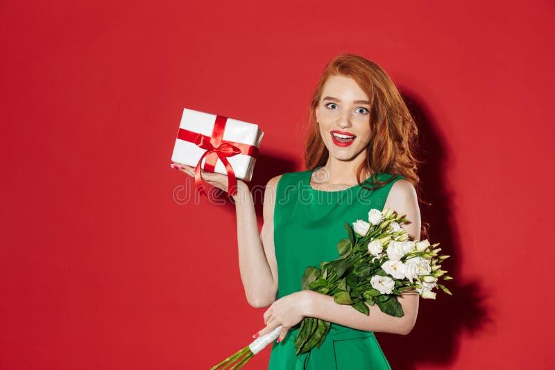 Redhead νέα ευτυχή κιβώτιο και λουλούδια δώρων εκμετάλλευσης κοριτσιών στοκ φωτογραφία με δικαίωμα ελεύθερης χρήσης
