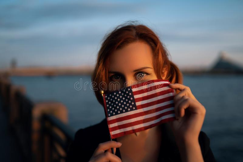Redhead πορτρέτο αμερικανικών σημαιών εκμετάλλευσης γυναικών στο ηλιοβασίλεμα από τον ποταμό - ταξιδιώτης και εξερευνητής στοκ εικόνα με δικαίωμα ελεύθερης χρήσης
