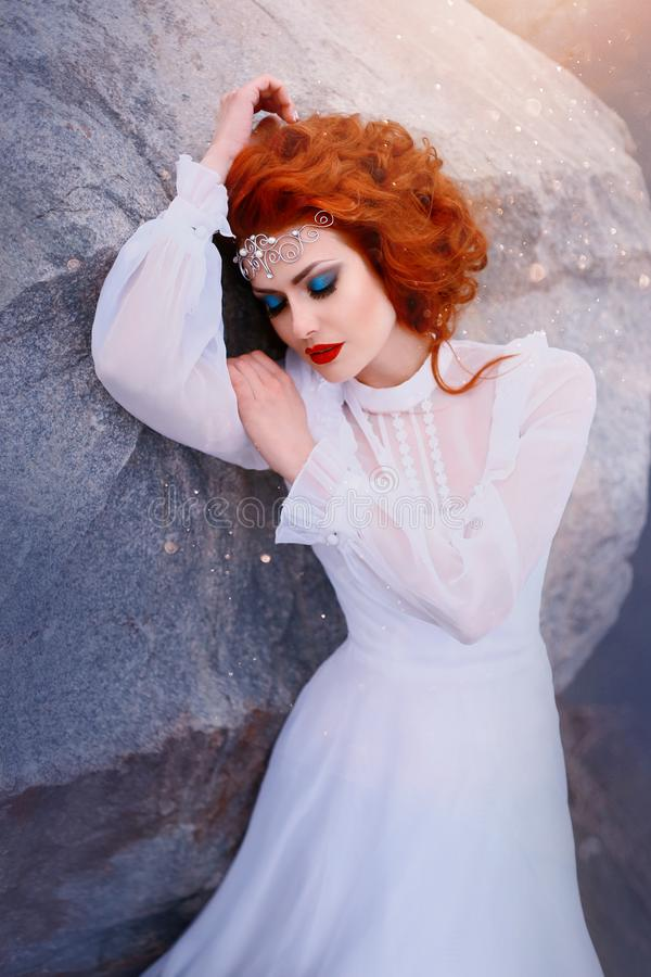 Redhead πριγκήπισσα σε ένα άσπρο εκλεκτής ποιότητας φόρεμα που βρίσκεται στις πέτρες Πολυτελής εξάρτηση με τα μανίκια αέρα Ομορφι στοκ φωτογραφία