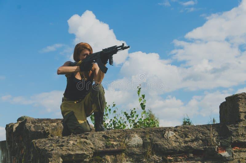 Redhead στάσεις κοριτσιών σε ένα γόνατο και στόχος από το όπλο στοκ εικόνα