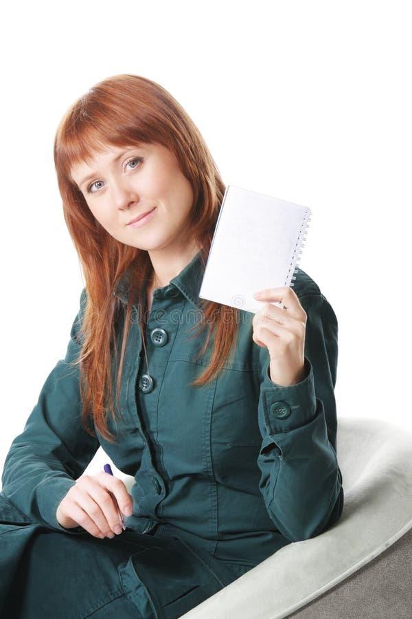 Redhead στην έδρα που εμφανίζει σημειωματάριο στοκ φωτογραφία