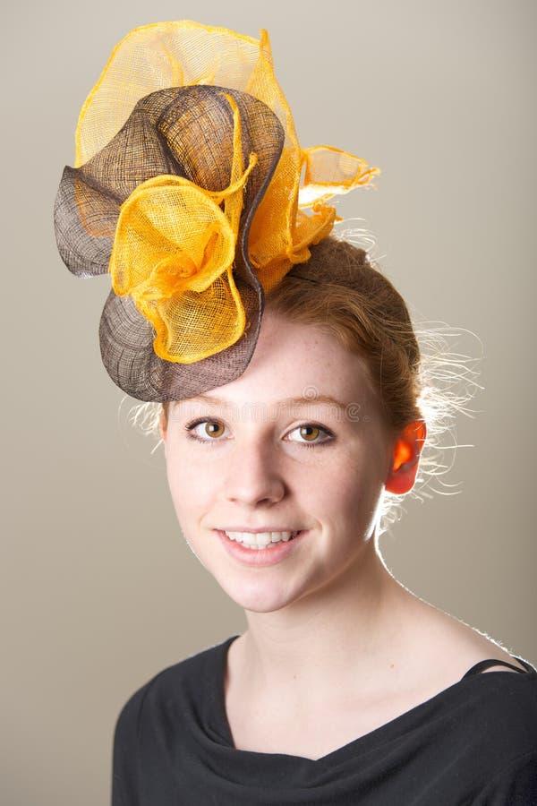 Redhead στο καλυμμένο μαύρο και πορτοκαλί καπέλο στοκ εικόνα