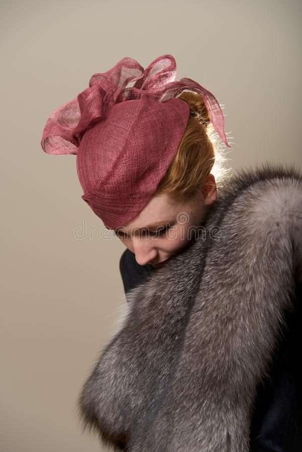 Redhead στο κόκκινο καπέλο πλέγματος που κοιτάζει κάτω στοκ φωτογραφία