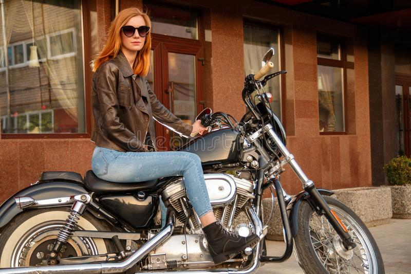 Redhead συνεδρίαση κοριτσιών σε μια μοτοσικλέτα στοκ εικόνα με δικαίωμα ελεύθερης χρήσης