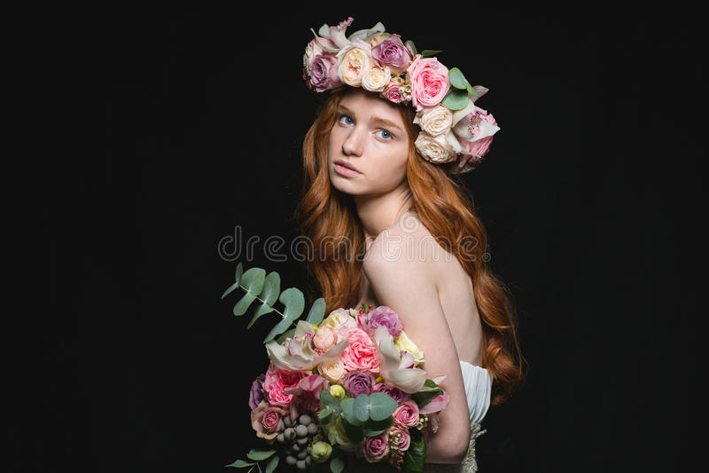 Redhead τοποθέτηση γυναικών Attrative με τα λουλούδια στοκ φωτογραφία με δικαίωμα ελεύθερης χρήσης