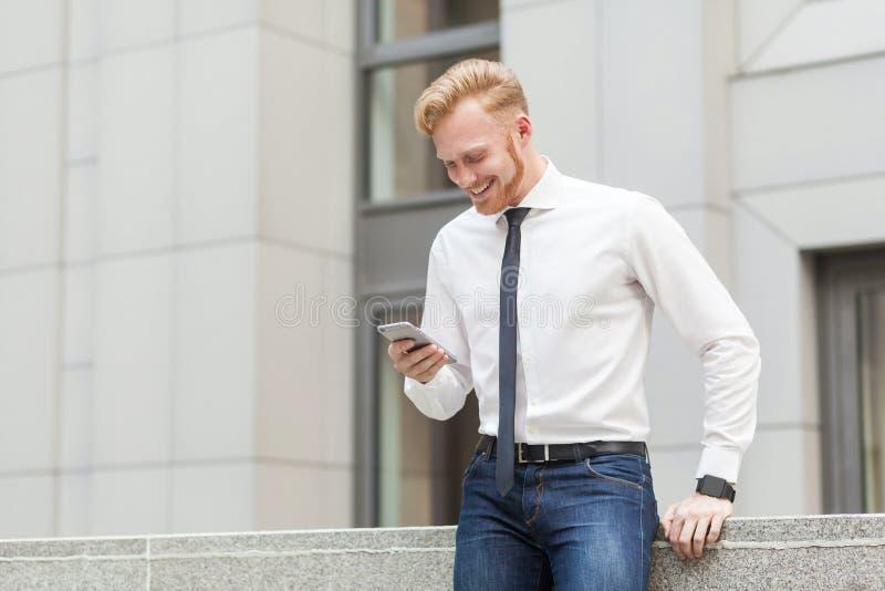Redhead и бородатый бизнесмен имеют видеоконференцию в телефоне hes умном владение домашнего ключа принципиальной схемы дела золо стоковые изображения