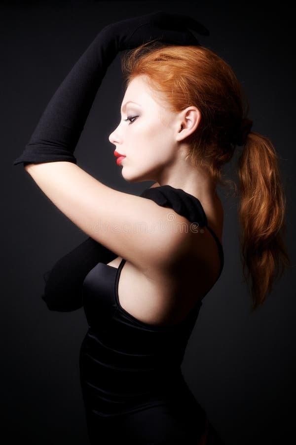 redhead привлекательной предпосылки темный модельный представляя стоковые фото