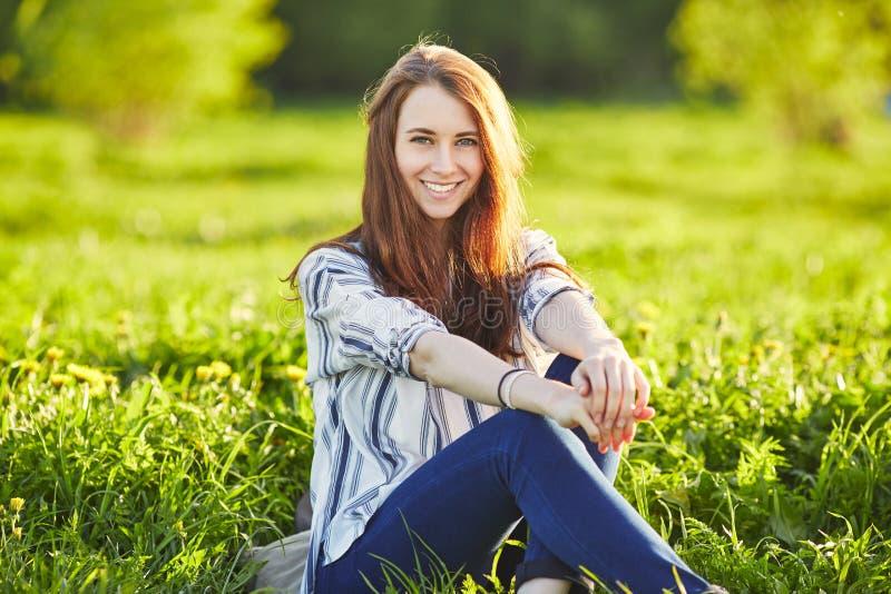 Η νέα όμορφη redhead γυναίκα κάθεται σε ένα πράσινο λιβάδι, εξετάζοντας τη κάμερα στοκ εικόνες