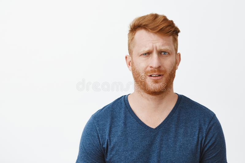 Redhead adult man in stupor cannot understand what happening, feeling clueless and questioned, lifting eyebrow and royalty free stock photo
