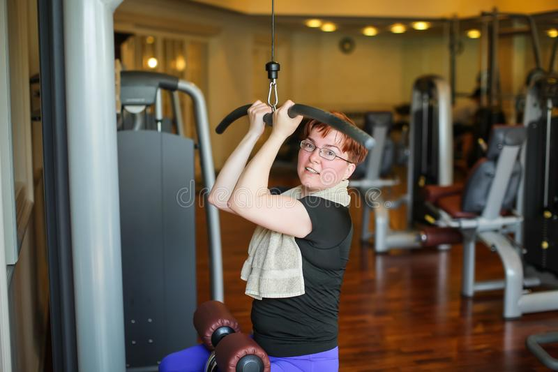 Redhead adult woman with short haircut execute exercise with exercise-machine in gym.  royalty free stock images
