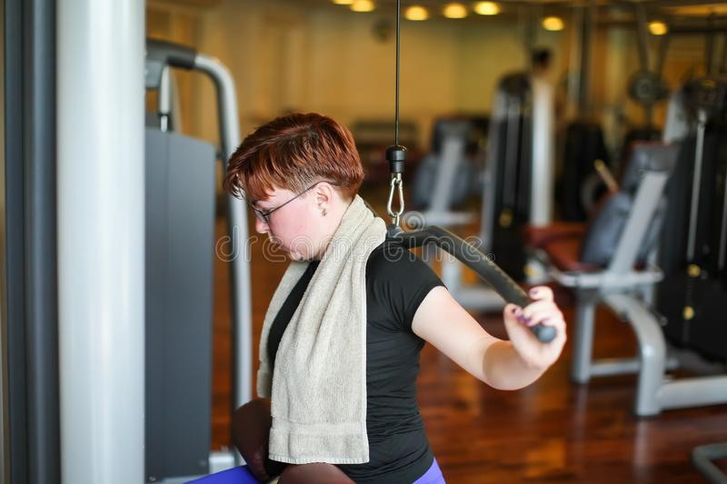 Redhead adult woman with short haircut execute exercise with exercise-machine in gym.  royalty free stock photos