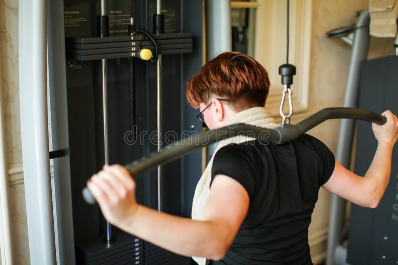 Redhead adult woman with short haircut execute exercise with exercise-machine in gym.  stock photos