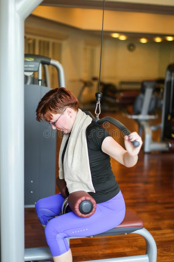 Redhead adult woman with short haircut execute exercise with exercise-machine in gym.  stock image