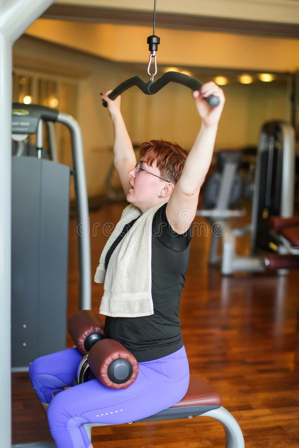 Redhead adult woman with short haircut execute exercise with exercise-machine in gym.  royalty free stock image