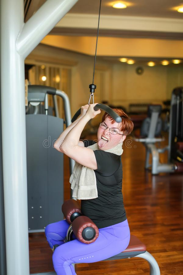 Redhead adult woman with short haircut execute exercise with exercise-machine in gym.  stock images