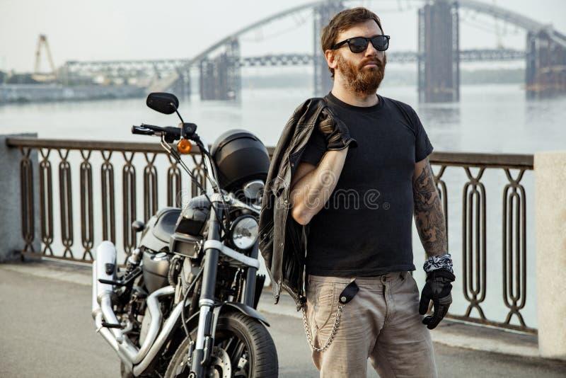 Redhead bearded biker holding leather jacket on shoulder and sta. Nding near motorbike on bridge royalty free stock photos