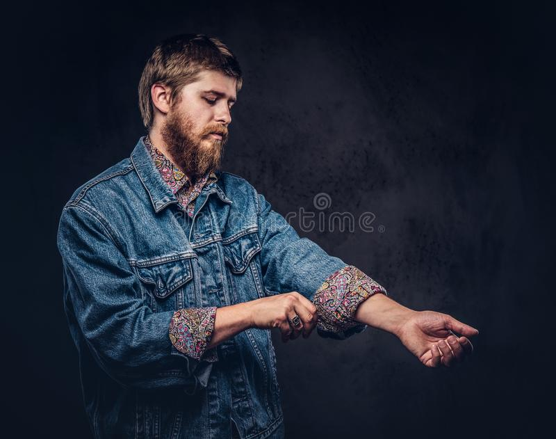 Redhead bearded guy dressed in jeans jacket roll up his sleeve on a dark background. Redhead bearded guy dressed in jeans jacket roll up his sleeve. Isolated on royalty free stock photos