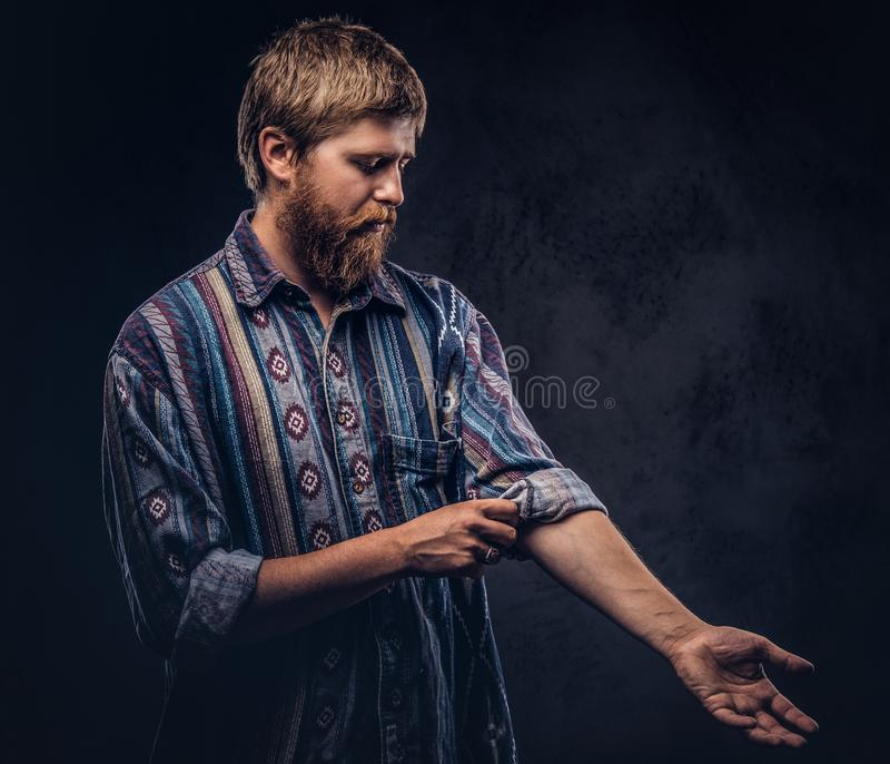 Redhead bearded guy dressed in an old-fashioned shirt roll up his sleeve on a dark background. Redhead bearded guy dressed in an old-fashioned shirt roll up his stock images